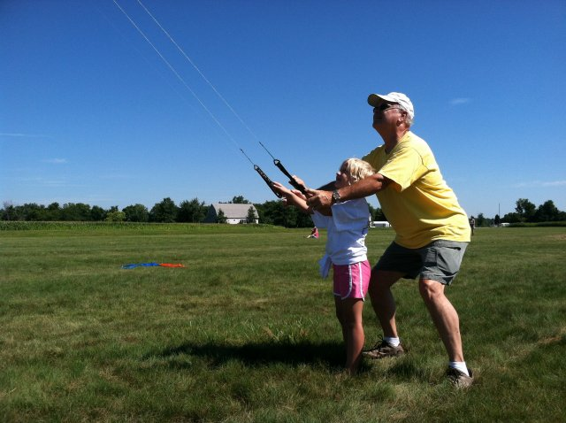 HKS member Dick Claycomb helps a child fly a dual-line sport kite